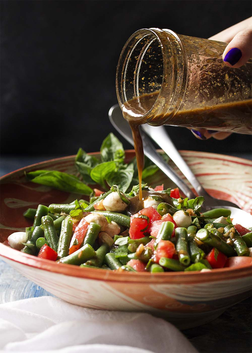Pouring basamic vinaigrette onto a bowl of Italian green bean and tomato salad.