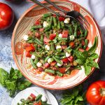 For an easy side dish which makes the most of fresh summer vegetables, you'll love this recipe for a cold Italian green bean and tomato salad! Green beans, tomatoes, basil, and mozzarella are all tossed in a sweet and tangy balsamic dressing. Great for bbqs, cookouts, and family dinners. | justalittlebitofbacon.com #summerrecipes #saladrecipes #greenbeans #italianrecipes #sidedish