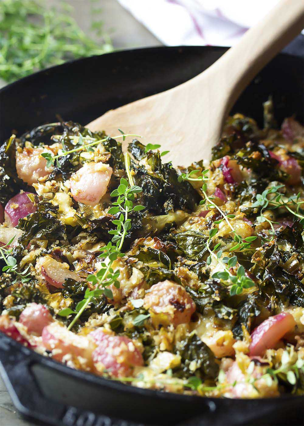A serving spoon scooping out a portion of kale, radish, and leek gratin from the cast iron pan.