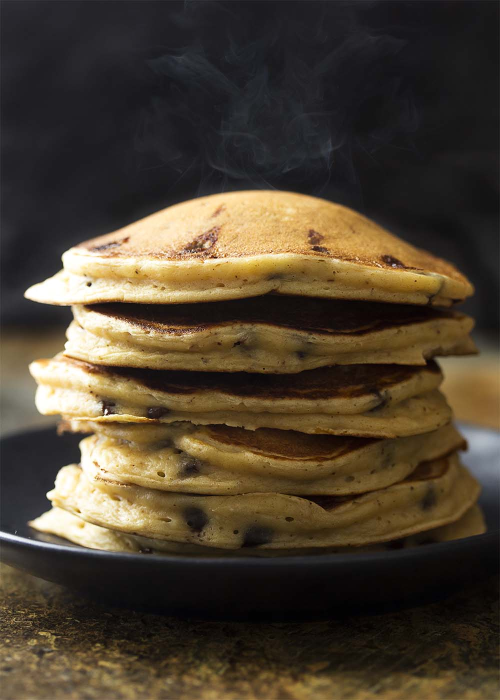 A hot stack of chocolate chip ricotta pancakes on a plate showing steam coming up off them.