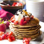 My fluffy ricotta pancakes are made with buttermilk and cannoli spices and studded with semi sweet chocolate chips! Top them with spiced strawberries, maple syrup, and whipped cream for a special weekend breakfast. | justalittlebitofbacon.com #italianrecipes #breakfastrecipes #pancakerecipes #pancakes #breakfast #cannoli