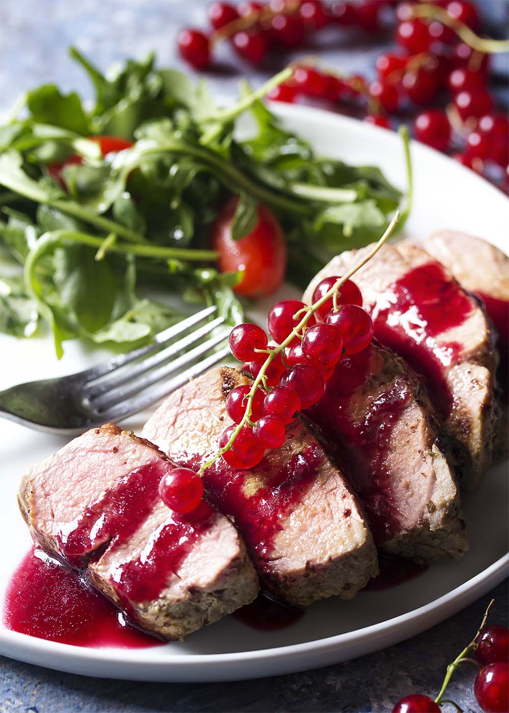 A plate with slices of roast pork tenderloin. The slices are topped with red currant sauce.