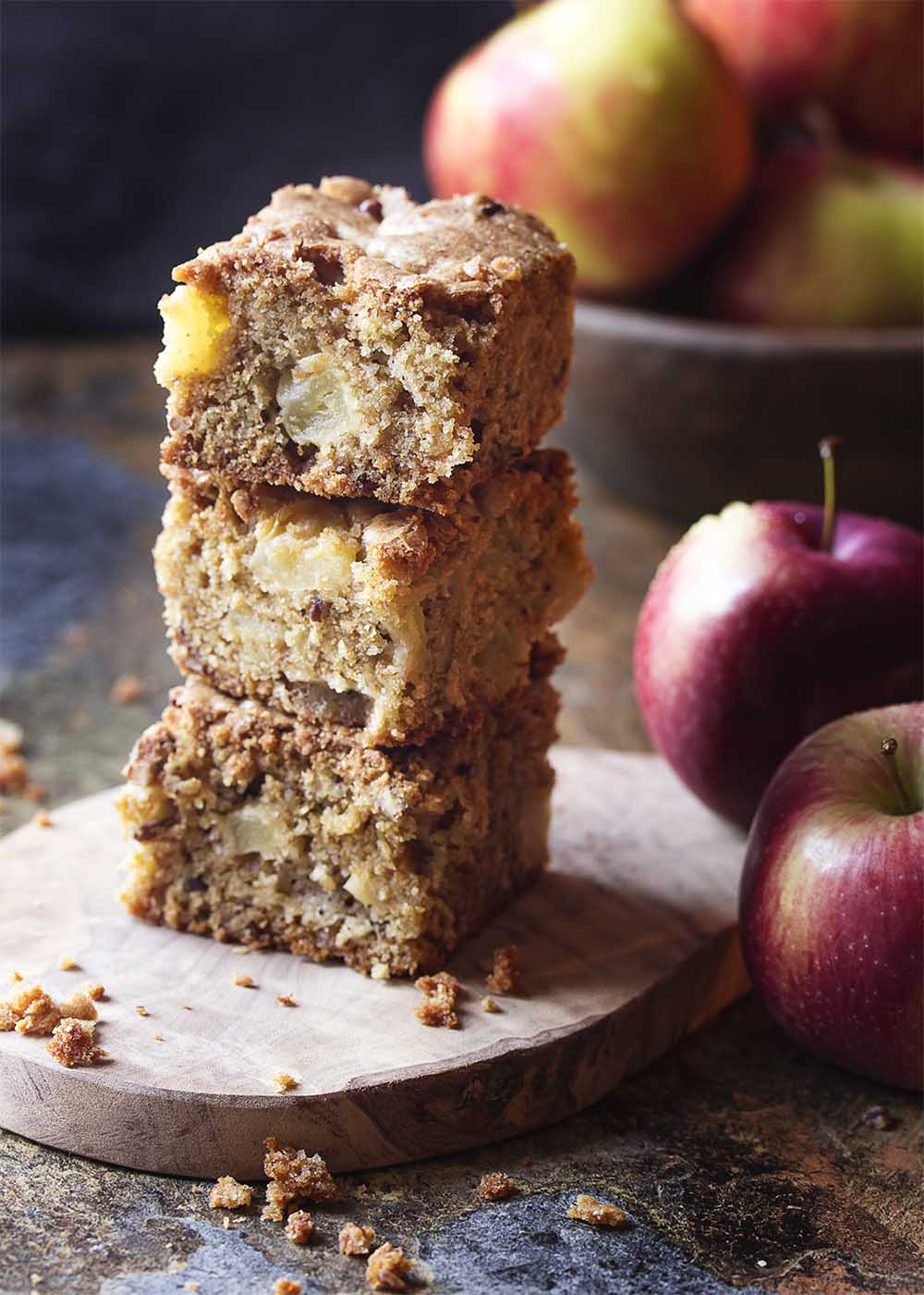 A stack of pieces of moist and delicious fresh apple cake on a wooden board.