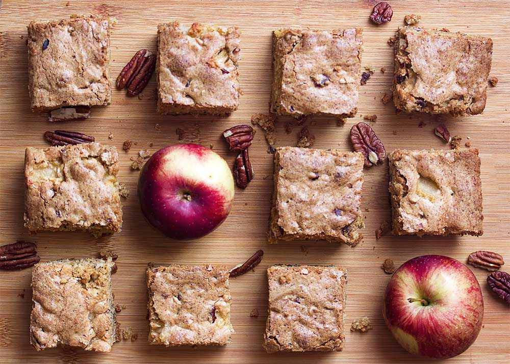 Pieces of fresh apple cake on a cutting board with pecans and apples scattered about.