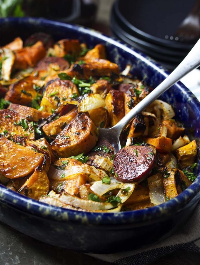 You'll love this ultimate one pot meal whether you call it chorizo or chourico! My Portuguese chorizo and sweet potato bake with onions and parsley is both delicious and simple to make. Just toss everything together and bake until the edges are crispy and potatoes are tender. | justalittlebitofbacon.com #portugeserecipes #spanishrecipes #chorizo #chourico #onepotmeals #easydinners