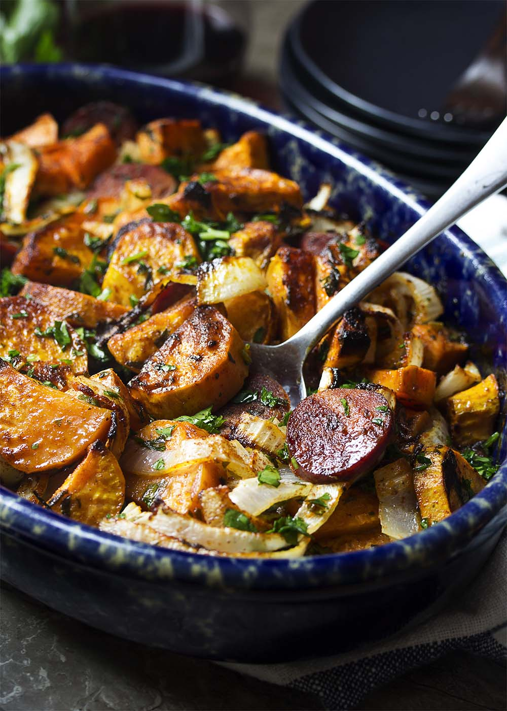 Close up of a casserole dish of delicious baked chorizo, sweet potatoes, and onions with a serving spoon ready to scoop out a portion.