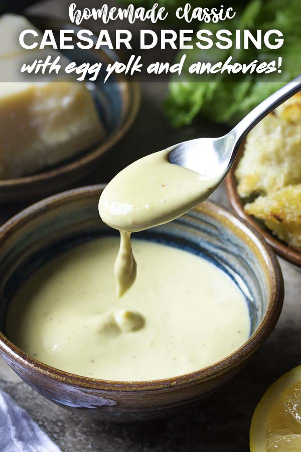 A spoon lifting dressing out of a bowl with text overlay - Caesar Dressing.