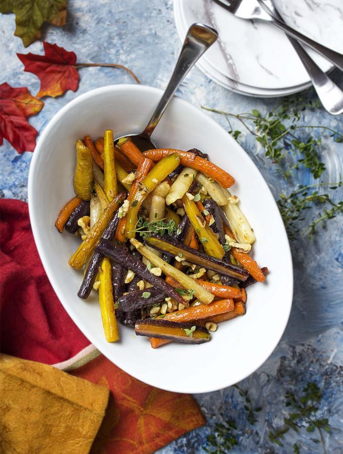 Sweet and tender, these glazed honey roasted carrots are tossed with balsamic, toasted walnuts, and fresh thyme to make a simple holiday side dish! | justalittlebitofbacon.com #holidayrecipes #sidedishrecipes #carrotrecipes #carrots #thanksgiving #christmas #easter