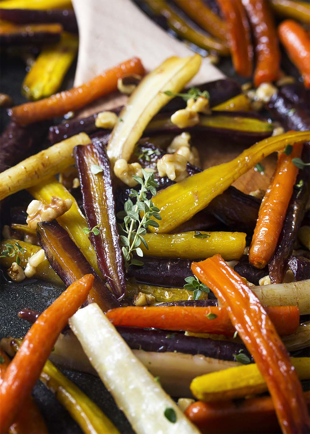 A roasting pan of roasted carrots glazed with honey and tossed with thyme, walnuts, and balsamic.