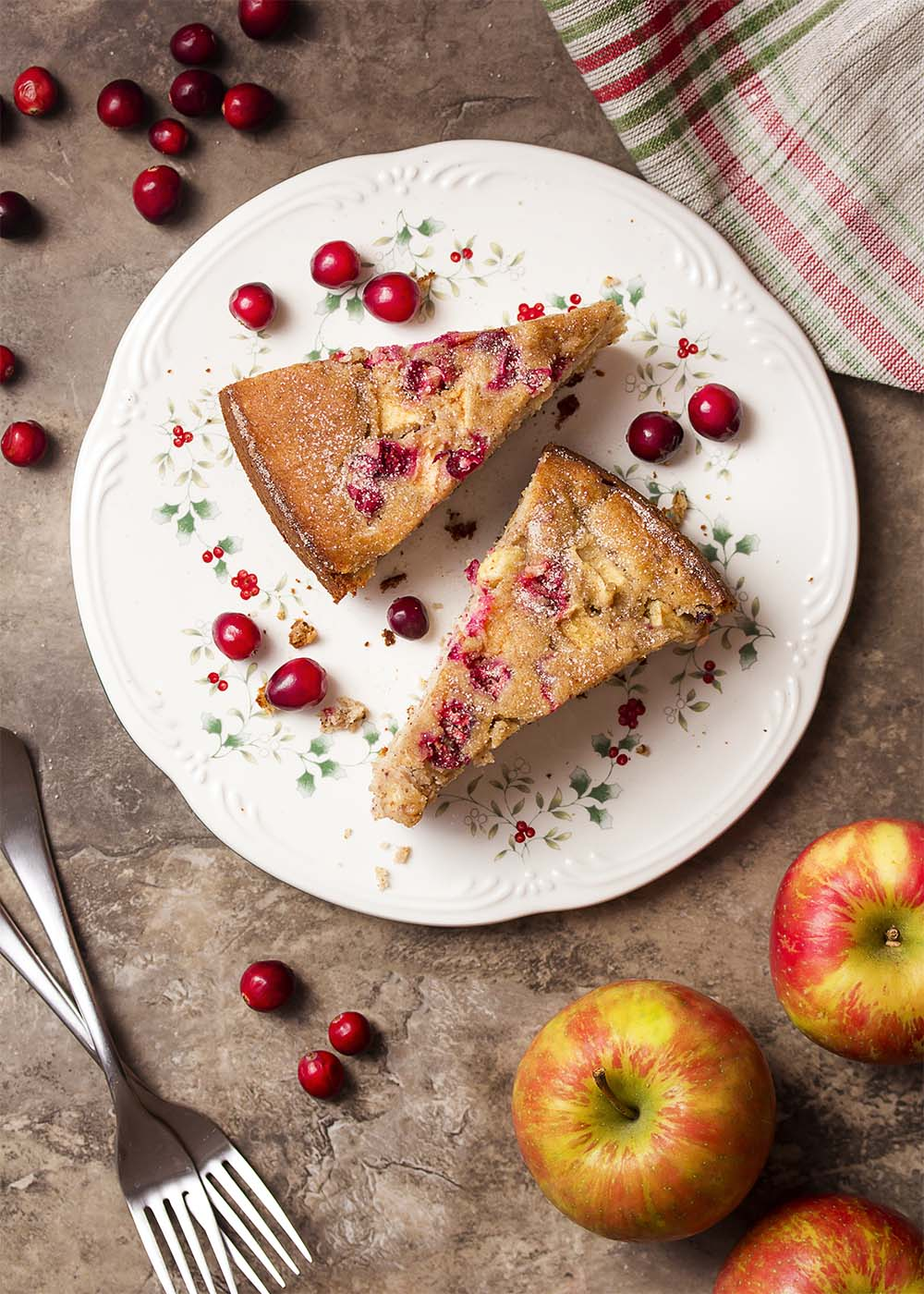 Top view of a serving plate with two slices of cranberry apple cake. Two forks on the table. Fresh cranberries and apples scattered about.