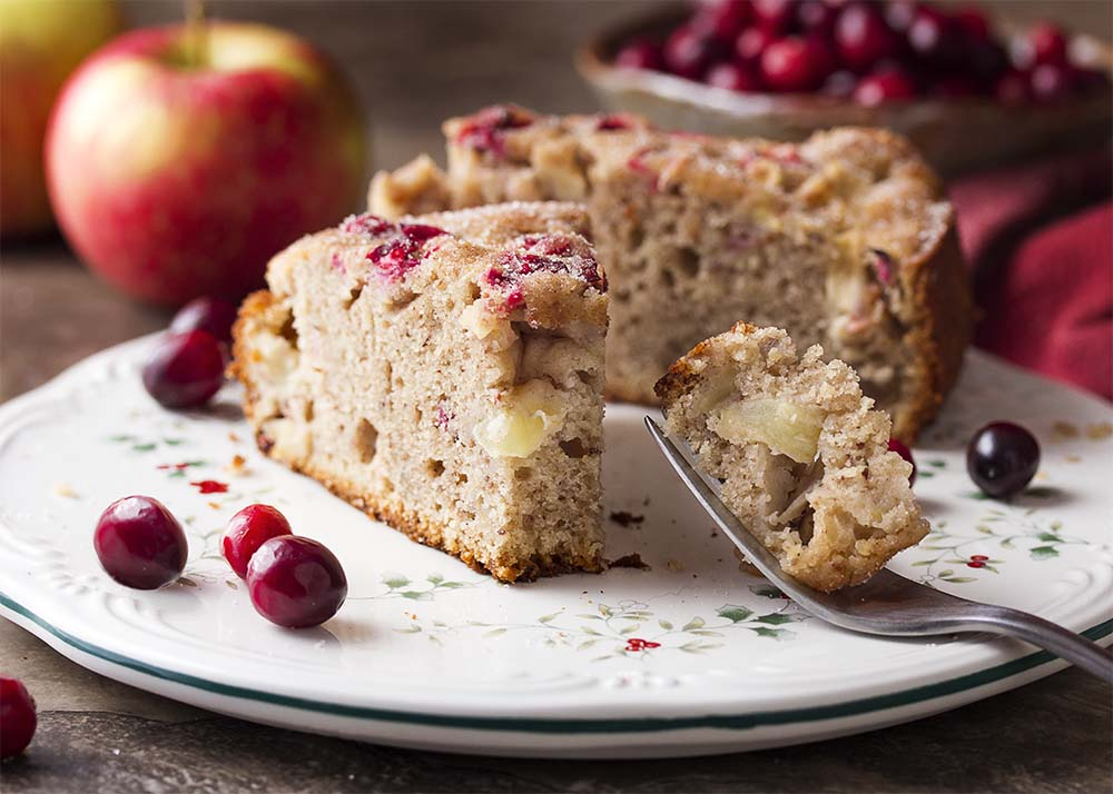 A piece of snack cake with cranberries and apples on a plate with a fork holding a portion to show the diced apples and cranberries in the cake.