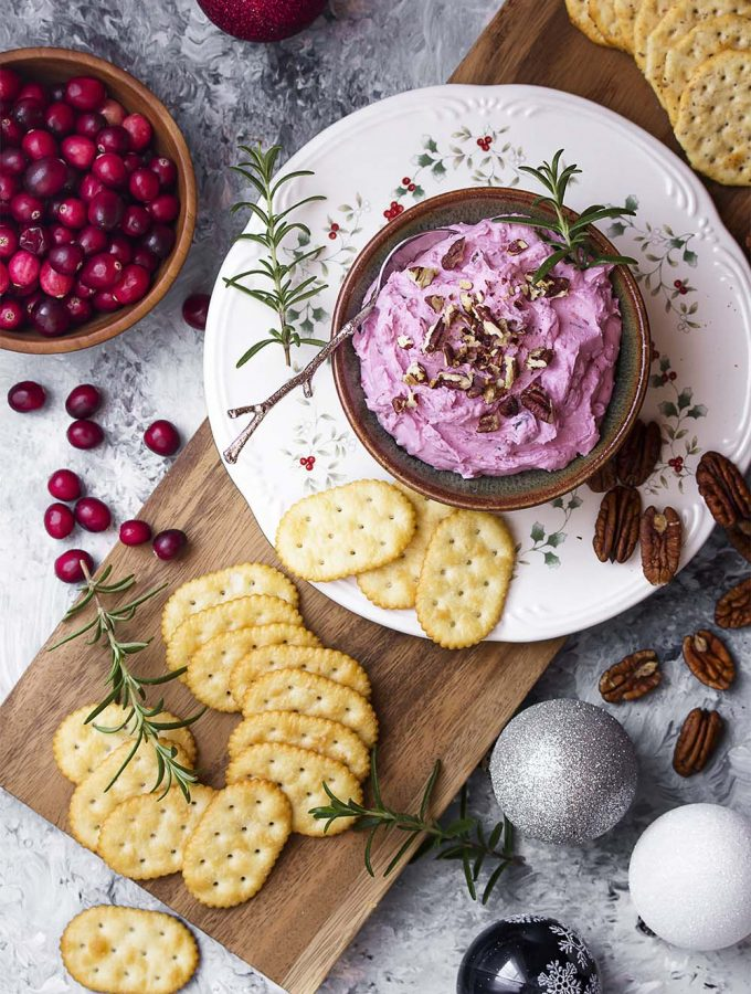 My cranberry goat cheese spread is an easy make ahead holiday appetizer! This cold dip is made of whipped goat cheese, fresh cranberry sauce, and toasted pecans. Wonderful for Christmas, New Years, Thanksgiving, and more.| justalittlebitofbacon.com #christmasrecipes #holidayrecipes #thanksgivingrecipes #appetizerrecipes #appetizer #cranberry #goatcheese