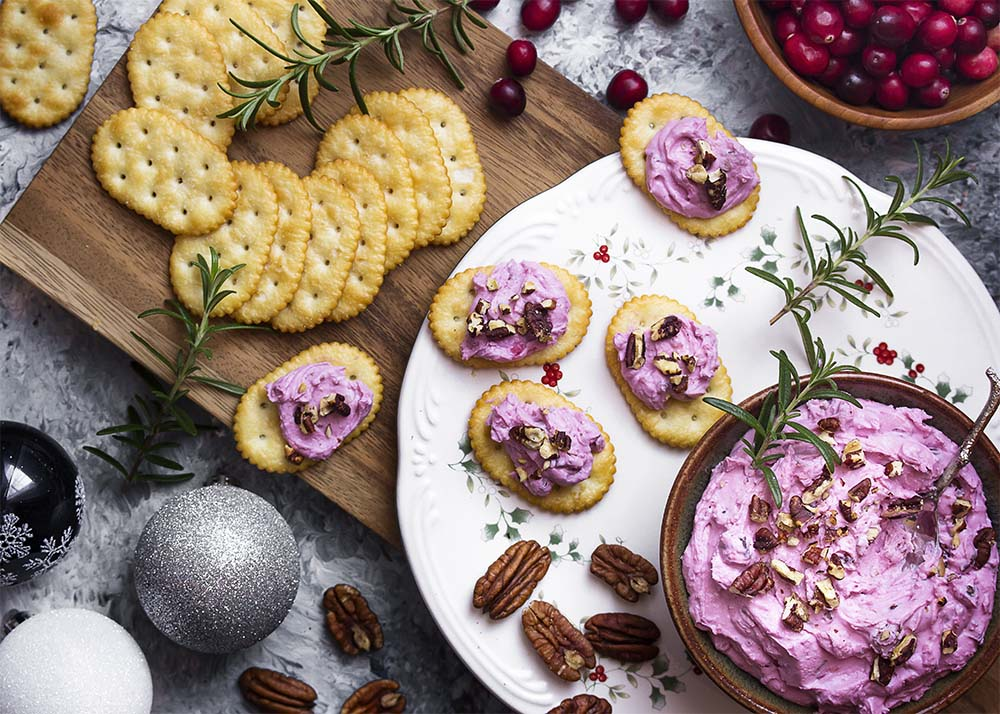 A bowl with cranberry goat cheese spread on a platter with crackers topped with the spread. More crackers, cranberries, and pecans, arranged around.