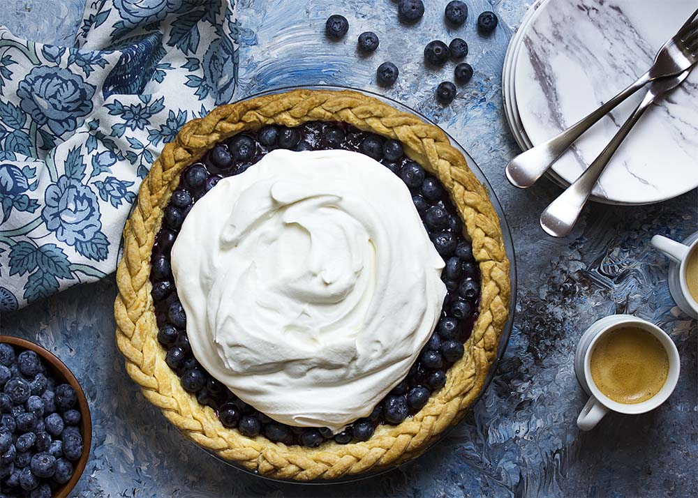 Top view of a fresh blueberry pie with a braided edge.