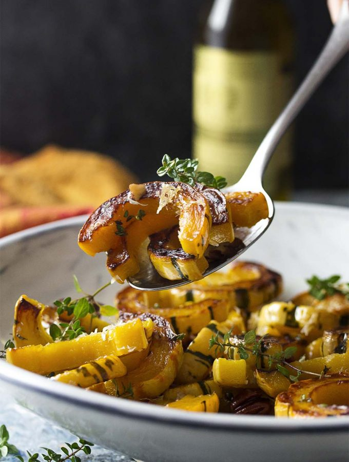 Learn how to cook roasted delicata squash with parmesan, pecans, and thyme! This healthy side dish bakes in the oven to make a simple side for a fall or winter dinner. | justalittlebitofbacon.com #delicatasquash #wintersquash #sidedishes #simplerecipes #roastsquash