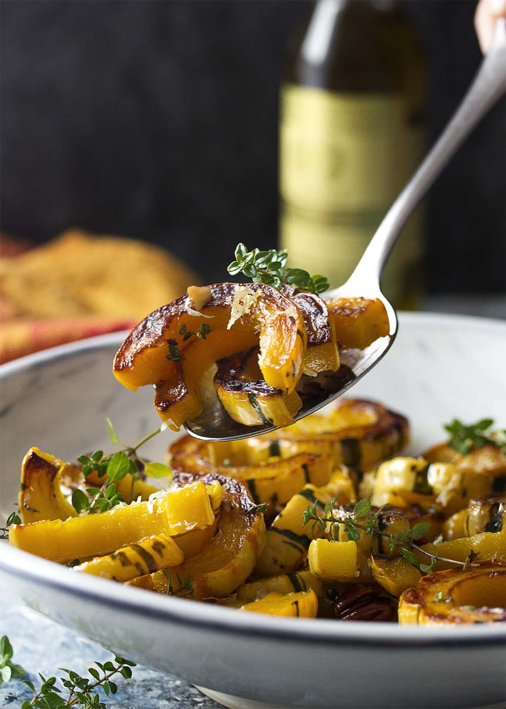 A spoon holding up several browned and roasted delicata squash rings from a serving bowl.