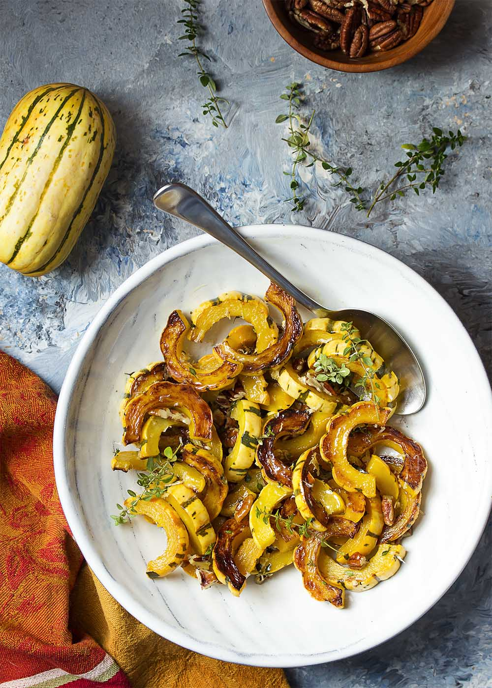 Top view of a serving bowl filled with roasted delicata squash, fresh thyme leaves, pecans.