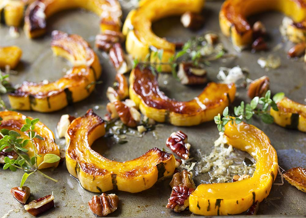 Deeply browned roasted delicata squash rings on a baking pan with thyme, pecans, and parmesan.