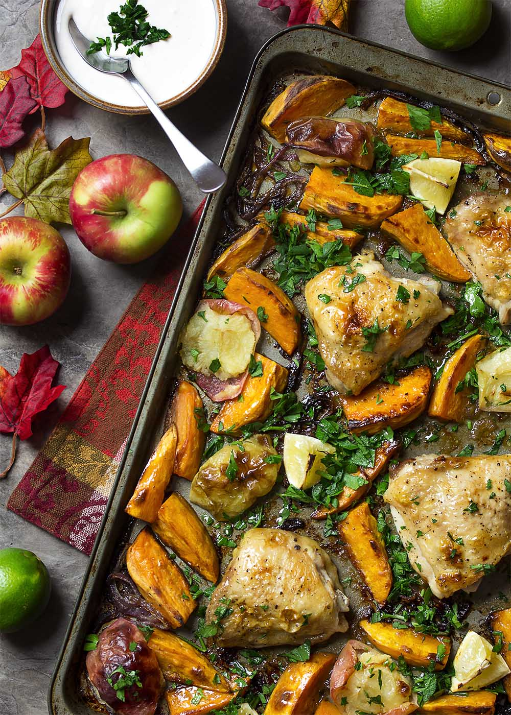 A sheet pan dinner full of golden brown baked chicken thighs, sweet potatoes, apples, and onions.