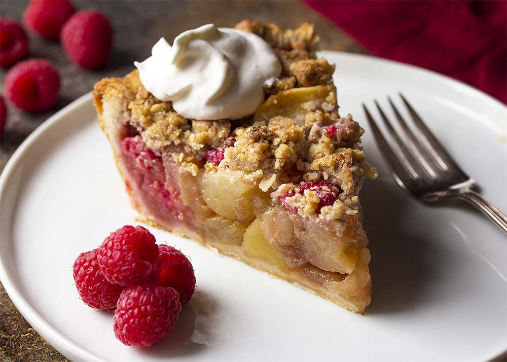 Side view of a slice of apple raspberry pie showing the slice apples and raspberries. Slice is topped with golden brown streusel and a dollop of whipped cream.