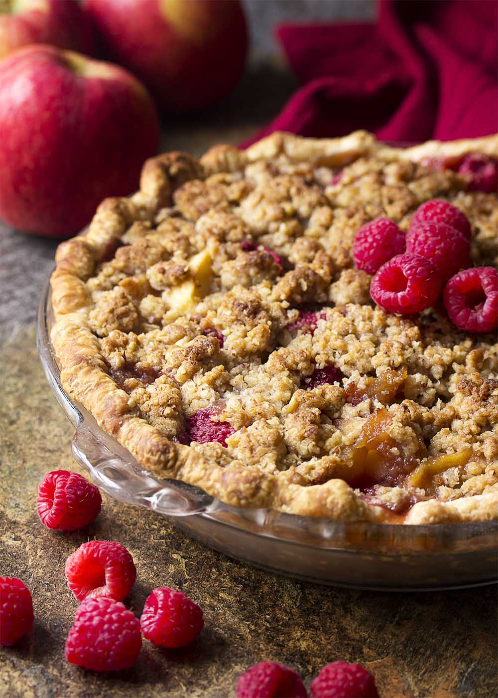 Close up of a freshly baked apple raspberry pie with crumb topping.