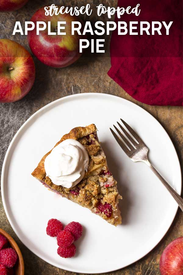 Slice of pie and whipped cream on a plate with text overlay - Apple Raspberry Pie.
