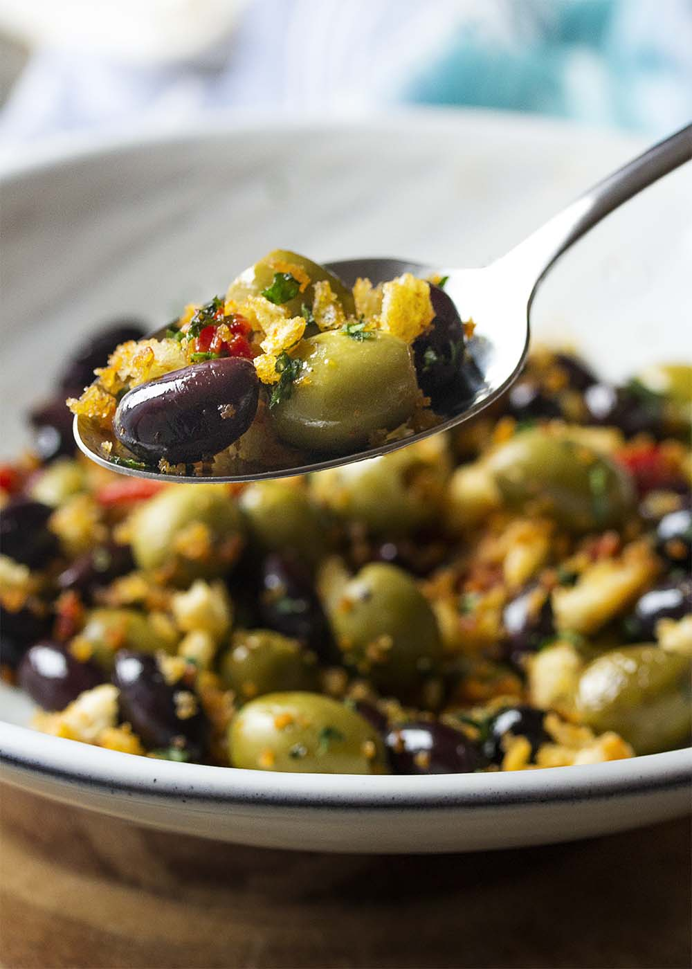A serving spoon holding up a scoop of olives with spiced bread crumbs.