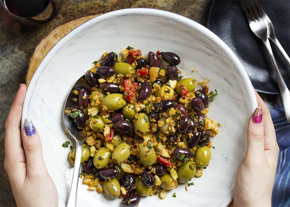 Hands holding up a serving bowl of black and green olive tapas.