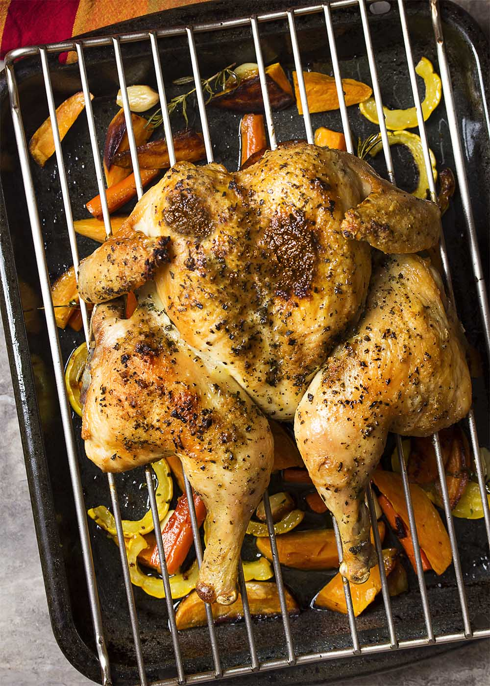 Roasted spatchcocked chicken on a rack in a roasting pan with roasted root vegetables.