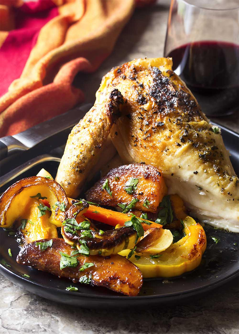 A portion of roasted chicken and root vegetables on a plate with a fork and knive and glass of wine.
