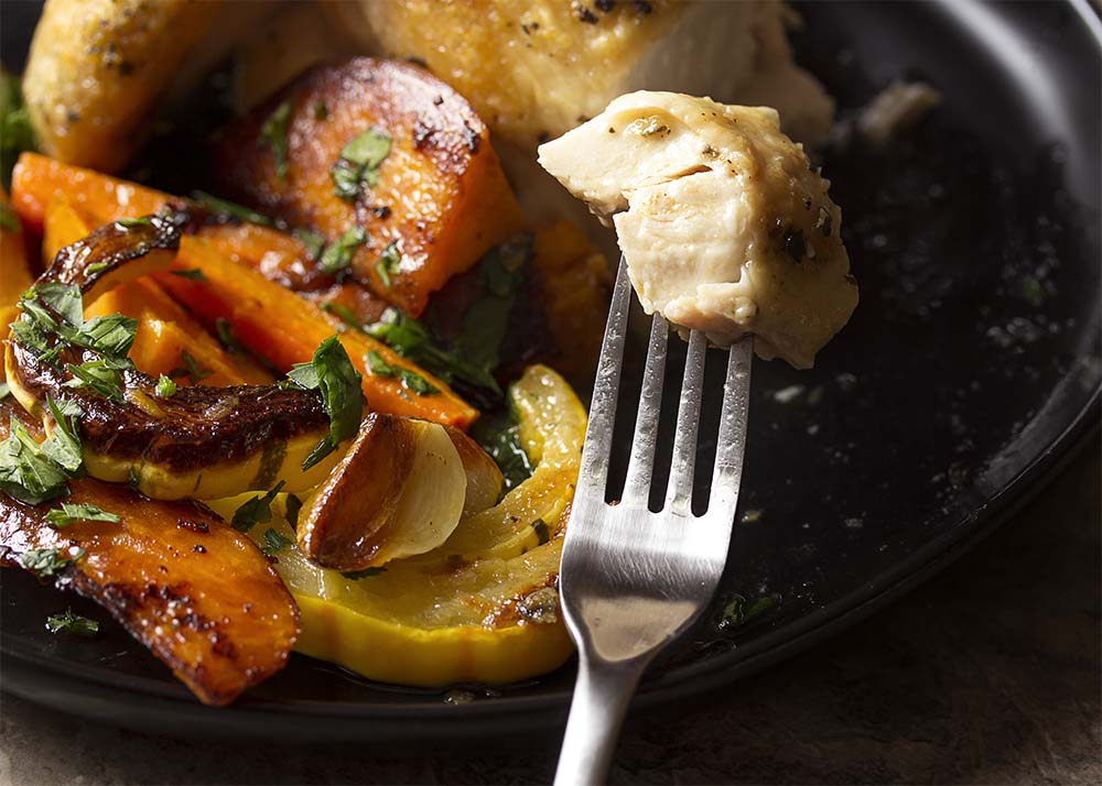 A fork holding up a piece of juicy roast chicken meat with a plate of roasted chicken and root vegetables in the background.