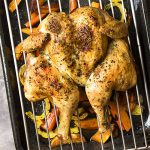 For simple oven roasted whole chicken with crispy skin and juicy meat, try my recipe for roasted spatchcocked chicken along with tender root vegetables! Great for Sunday dinner, Christmas, Thanksgiving, Easter, and any other holidays. | justalittlebitofbacon.com #roastchicken #chickendinner #chickenrecipes #christmasrecipes #holidayrecipes #thanksgivingrecipes