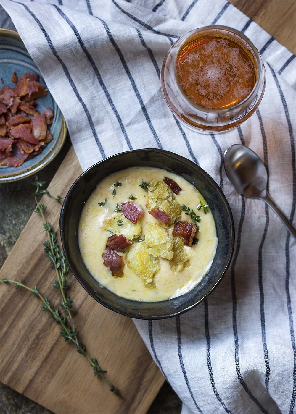 Top view of a bowl of creamy bacon cheddar soup topped with croutons and bacon crumbles. A glass of beer, a cloth napkin, and a spoon on the table.