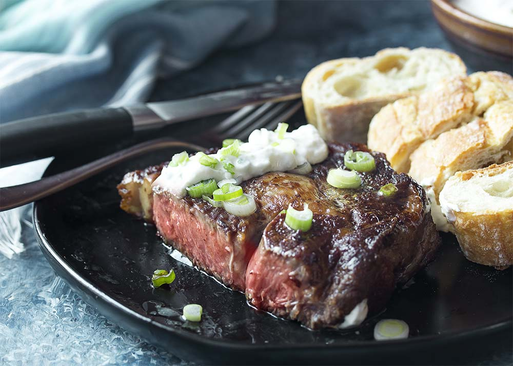 Seared ribeye on a plate with horseradish sauce and bread. The steak is cut open to show the perfect medium rare interior.