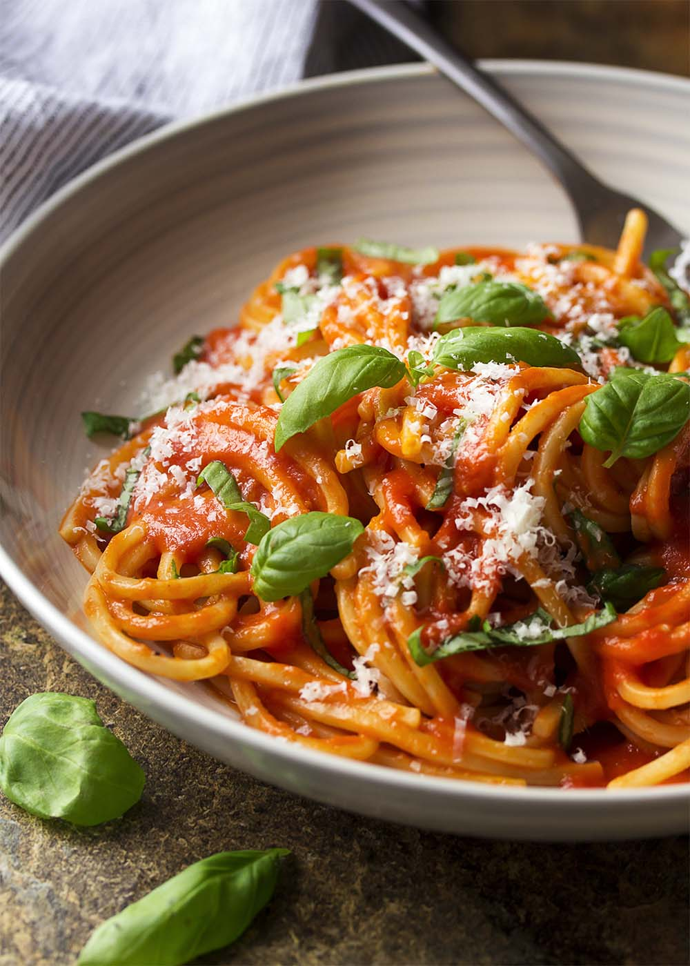 A bowl of pasta al pomodoro showing thick spaghetti topped with tomato sauce, basil leaves, and shredded parmesan cheese.