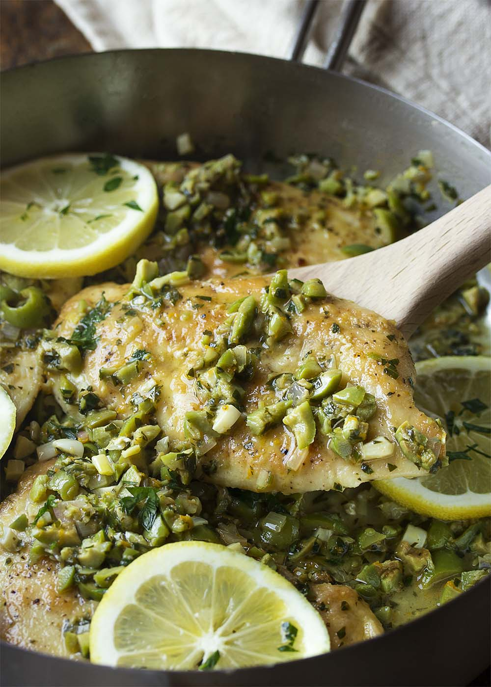 A skillet filled with golden brown chicken breasts topped with chopped green olives in a gremolata sauce.