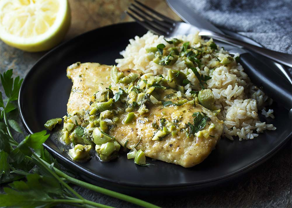 Tender pan fried chicken breast on a black plate with brown rice. Olive, citrus, and parsley sauce over the top.