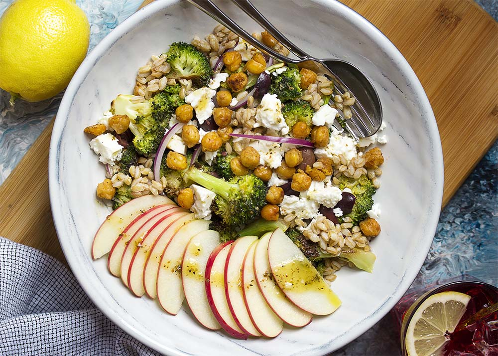Closeup of a bowl of salad with farro, chickpeas, broccoli, feta, olives, and apples.