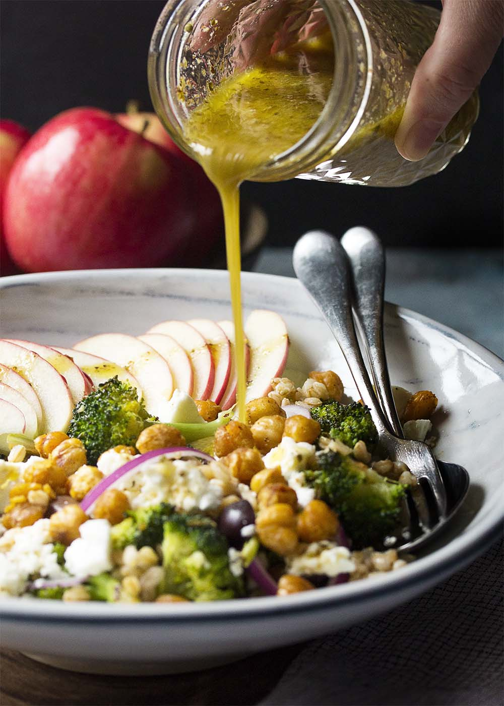 Pouring Greek dressing onto the Mediterranean farro salad with roasted broccoli, chickpeas, and apples.
