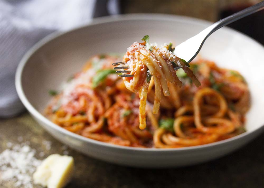 A fork holding spaghetti with tomato sauce twirled around it. Pasta is topped with parmesan cheese and basil. A bowl of pasta in the background.