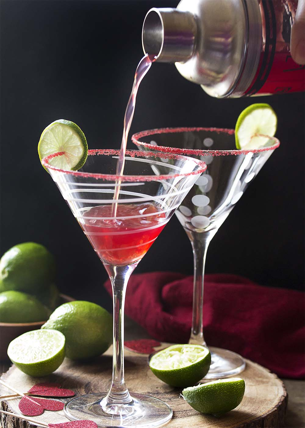 Pouring the cocktail from a shaker into a martini glass. The glass is garnished with lime and a red sugar rim. Cut limes scattered about.
