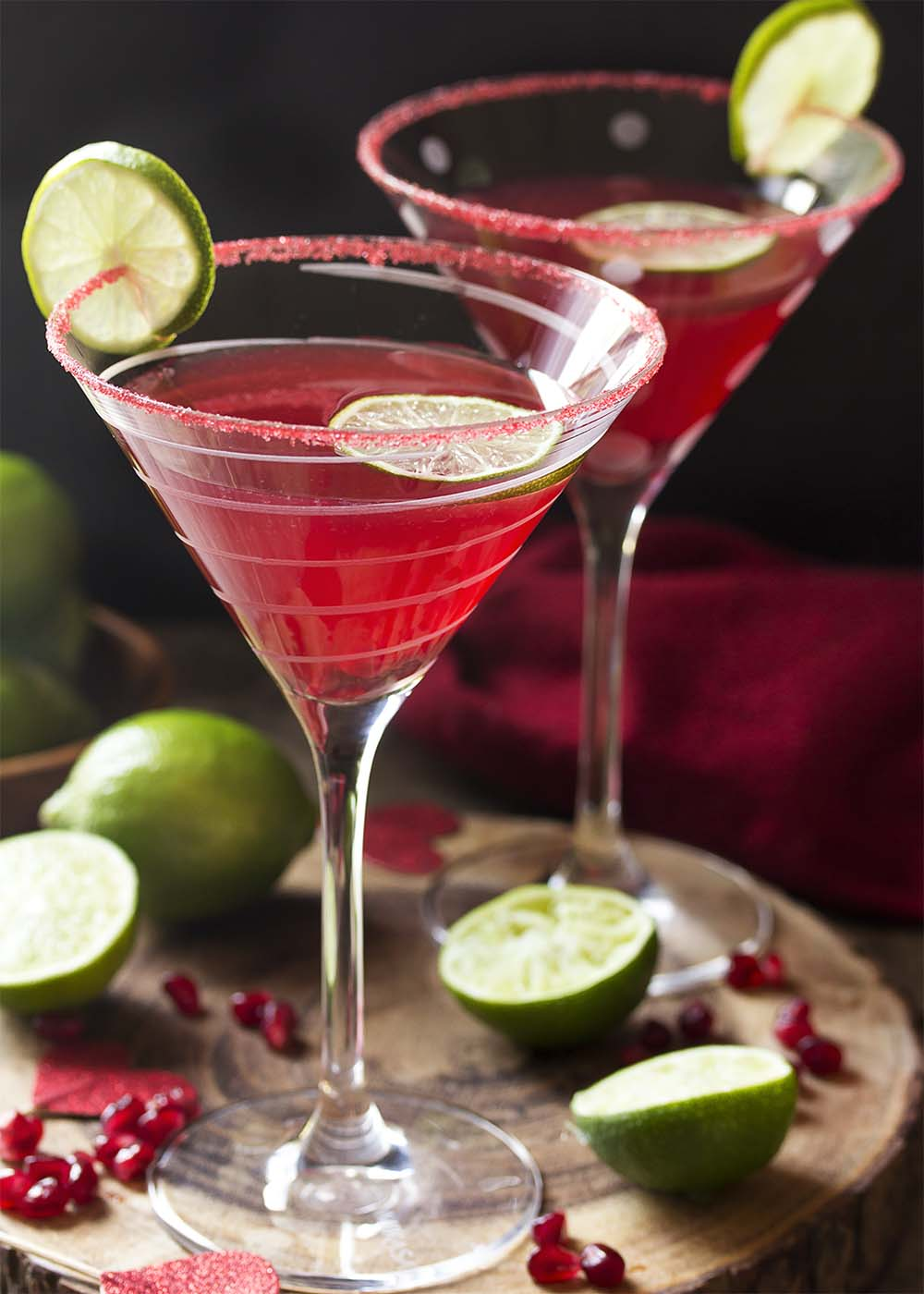 Two glasses of pomegranate martini with limes, pom arils, and red hearts around.