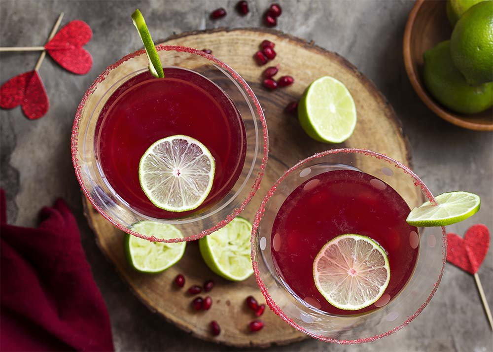 Top view of two pomegranate cocktails each garnished with lime and rimmed with red sugar. Limes, pom arils, and red hearts scattered about.
