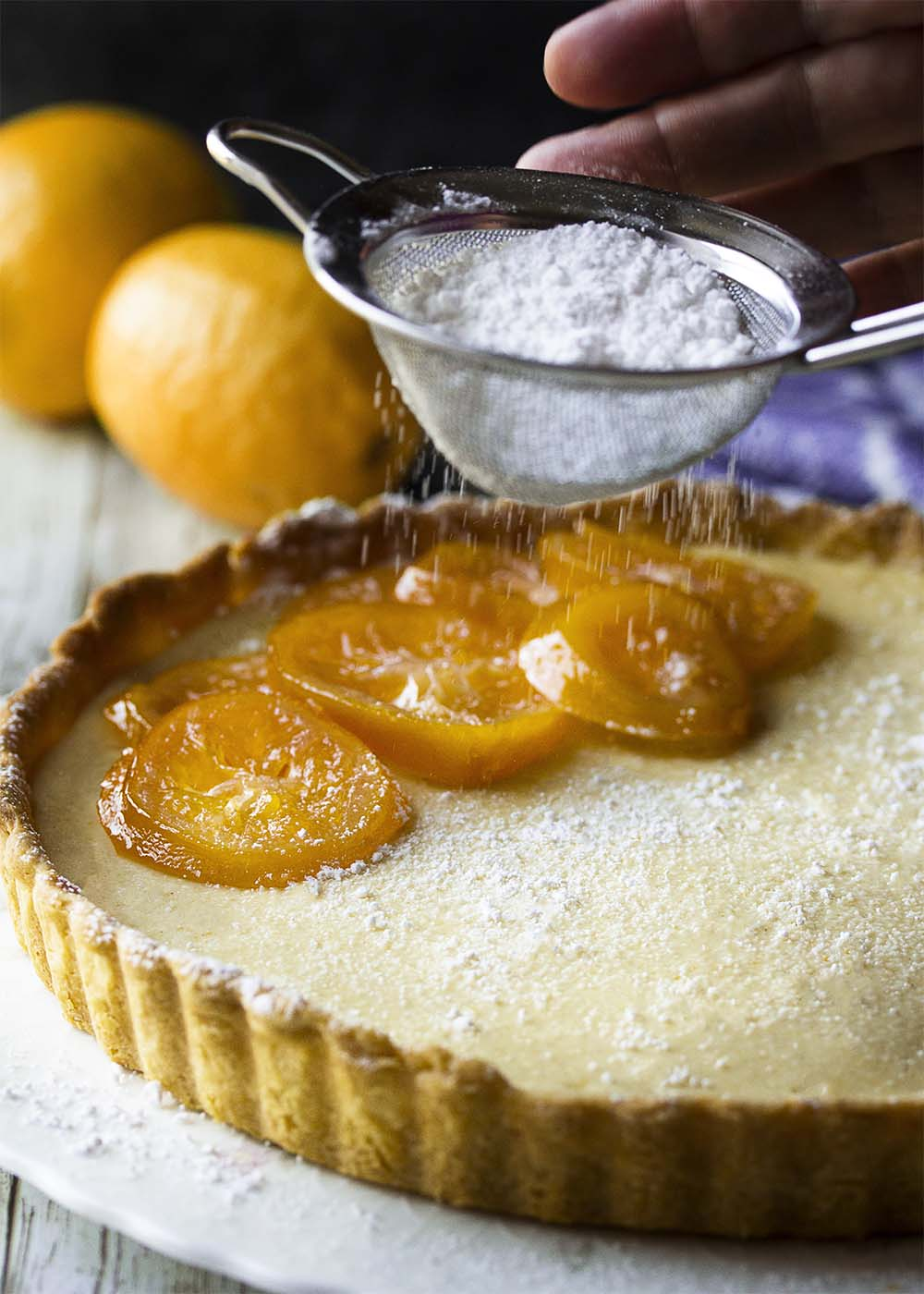A hand shaking powdered sugar onto the top of an Italian lemon ricotta pie. Pie decorated with candied lemon slices. Whole lemons in the background.