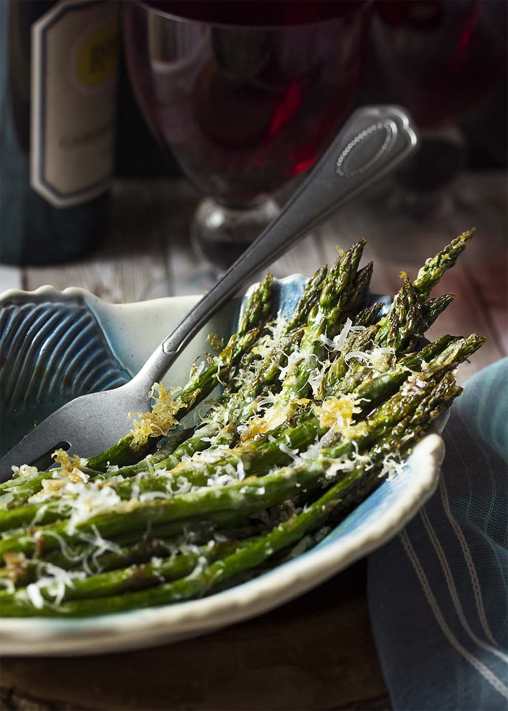 A serving dish filled with asparagus. A serving fork in the dish. Wine bottle and glasses in the background.