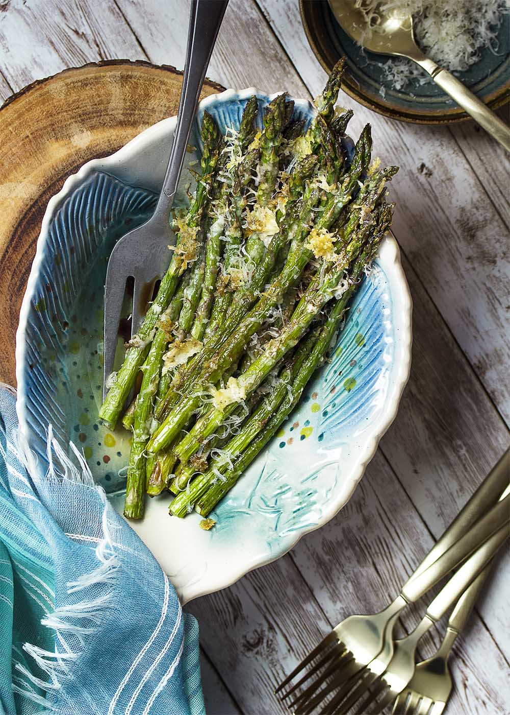 A serving bowl filled with roasted asparagus topped with crispy parmesan. Serving fork in the bowl. More forks on the table.