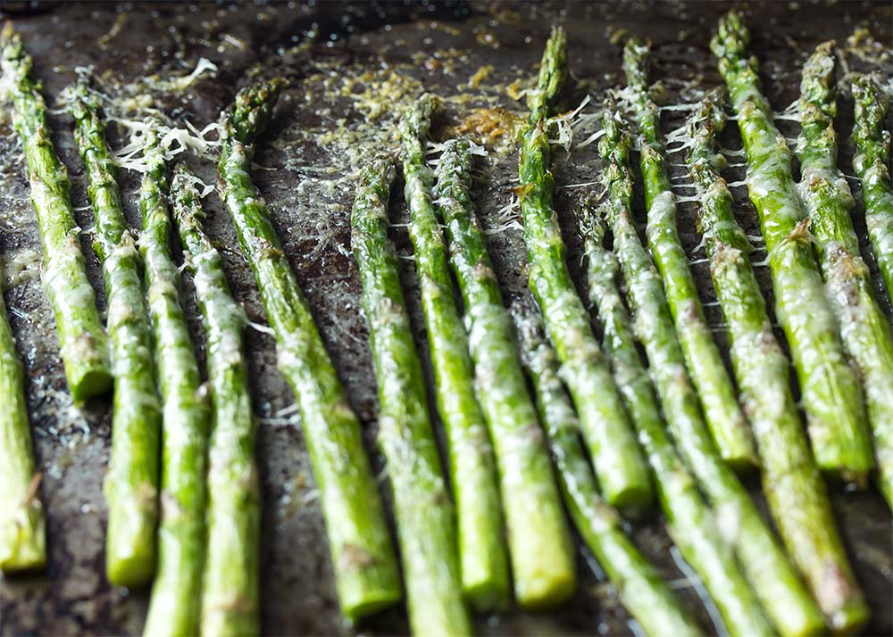 Asparagus spears lined up on a baking tray and topped with parmesan.