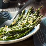 For an easy and quick side dish, cook my oven roasted asparagus with parmesan! This delicious Mediterranean recipe makes delicious use of spring produce with crispy cheese, tender veggies, and a sprinkle of balsamic. | justalittlebitofbacon.com #italianrecipes #italianfood #mediterraneanfood #springrecipes #asparagus #spring