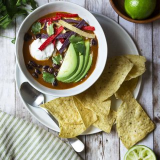 My spicy vegetarian tortilla soup is easy, healthy, AND quick! This is a pantry meal you can make in 30 minutes for a delicious and satifying dinner. Rich broth, smoky chipotles, plenty of black beans, and crunchy tortilla chips. | justalittlebitofbacon.com #mexicanfood #mexicanrecipes #souprecipes #pantryrecipes #soup #mexican #blackbeans #vegetariandinners