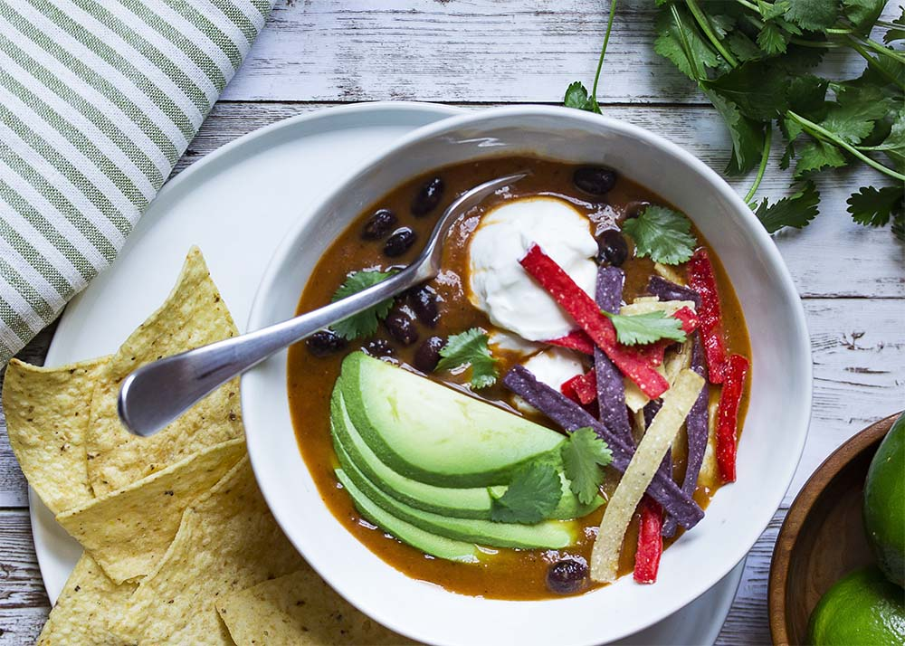 Top view of a table with a bowl of black bean tortilla soup on a plate with tortilla chips. Soup topped with avocado, cilantro, and sour cream.